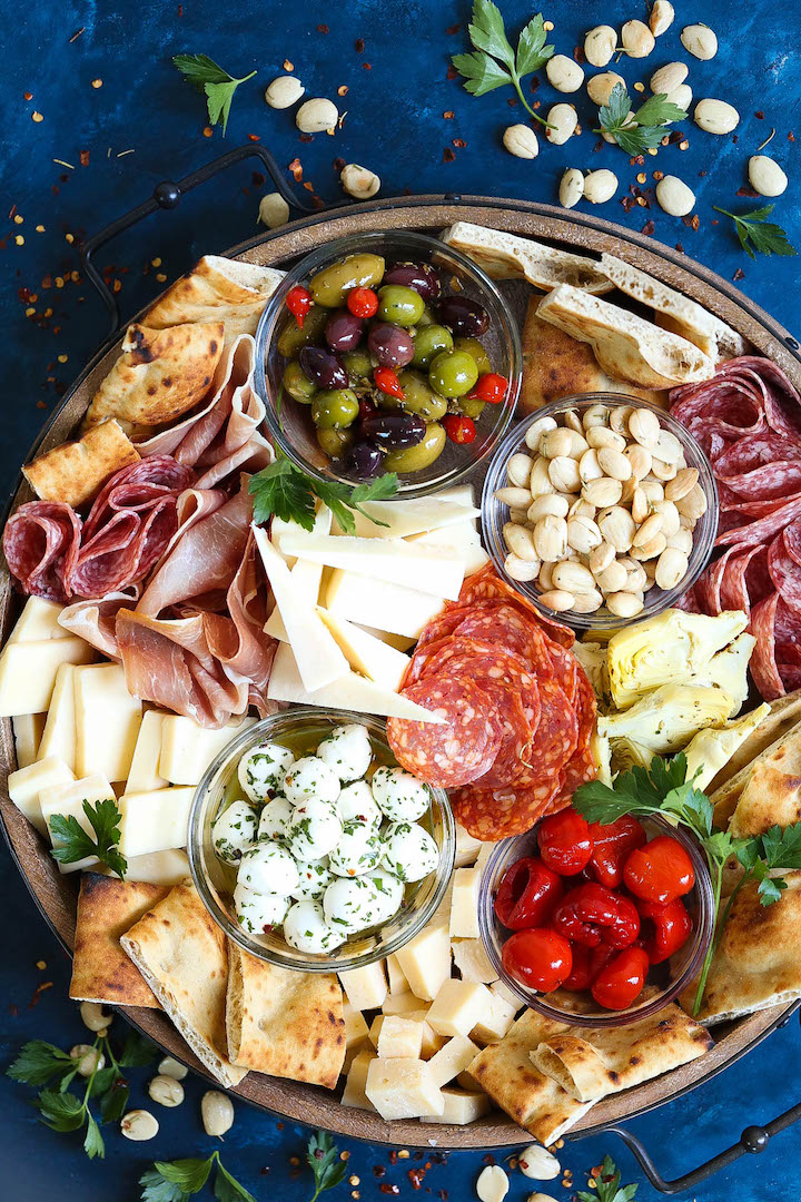 Antipasto Appetizer Cheese Board - Learn how to build the absolute PERFECT antipasto platter! It's unbelievably easy and sure to be a crowd-pleaser for all your guests! Served with cured meats, fresh cheeses, artichoke hearts, olives, nuts, peppers and focaccia!